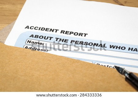 Accident report application form and pen on brown envelope, business insurance and risk concept; document is mock-up - stock photo