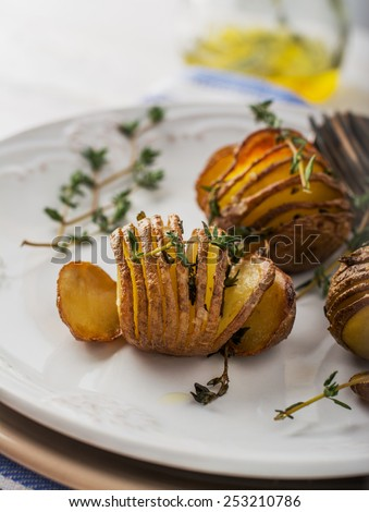 Accordion baked potatoes with thyme and sea salt in the oven. Portions served with a sprig of fresh thyme on a light dish. Selective focus. - stock photo