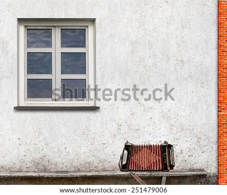 accordion on the bench near the wall with a window background - stock photo