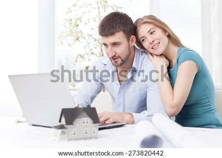 Accountancy. Young couple paying with credit card for online shopping - stock photo