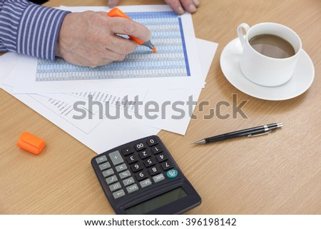 Accountant busy at his desk using an orange highlighter on a spreadsheet - stock photo