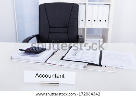 Accountant Name Plate On Desk With Empty Chair - stock photo