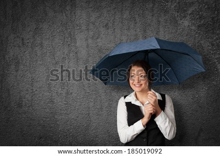 Accountant woman get cute with tax. Sly businesswoman hide and protect herself under umbrella against raining tax. Tax optimization concept. - stock photo