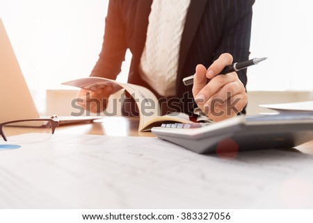 Accountant women using a calculator to calculate the numbers for bookkeeping or audit. - stock photo