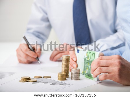 Accountants calculating profit - closeup shot of hands counting banknotes and coins and making notes on paper - stock photo