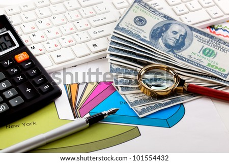 Accounting. Calculator Keyboard and magnifying glass near the money