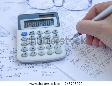 Accounting concept.Calculator with finance papers and man hand with pen