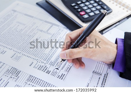 Accounting concept - Hands writing on paper with calculator in office
