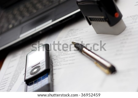 Accounting Table Setting - Mobile phone paperwork - stock photo