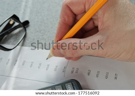 accounting work with pencil, calculator and glasses
