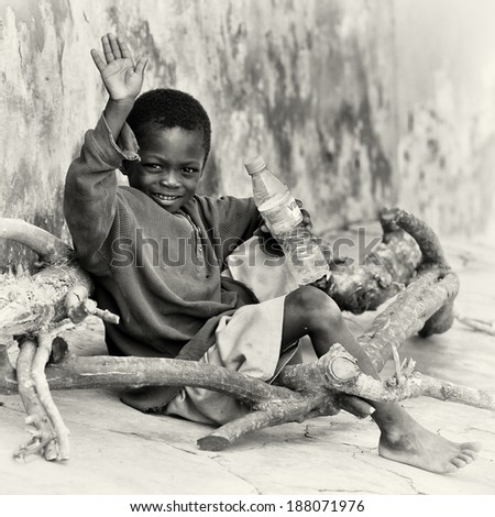 ACCRA, GHANA - MAR 5, 2012: Unidentified Ghanaian boy sits with a bottle of water sits in the street. People of Ghana suffer of poverty due to the difficult economic situation - stock photo