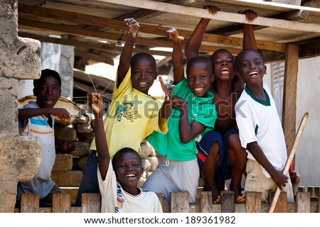 ACCRA, GHANA - MARCH 18: Unidentified african boys greeting to tourists with smiling faces  on May 18, 2014 in Teshie community, Accra, Ghana. Teshie is the famous fishing community in Ghana.