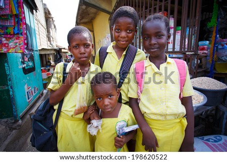 ACCRA, GHANA - MARCH 18: Unidentified African students greeting to tourists after school   on March 18, 2014 near Nima, Accra, Ghana, Nima is one of the most deprived community in Ghana.