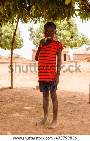 ACCRA, GHANA - MARCH 6, 2012: Unidentified Ghanaian boy in a red shirt in the street in Ghana. Children of Ghana suffer of poverty due to the unstable economic situation