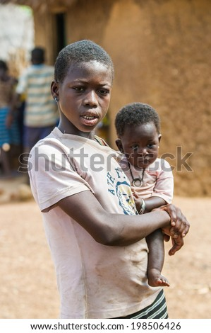 ACCRA, GHANA - MARCH 6, 2012: Unidentified Ghanaian mother carries her little baby on her arms in the street in Ghana. Children of Ghana suffer of poverty due to the unstable economic situation