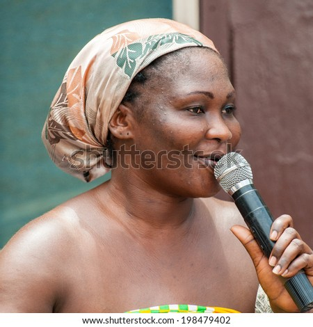 ACCRA, GHANA - MARCH 4, 2012: Unidentified Ghanaian woman sings a song at the local street music show in Ghana. Music is the main kind of entertainment in Africa