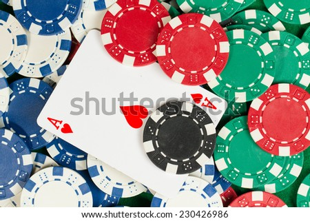 Ace card in the middle of green, red, blue, white and black Playing Poker Chips in a green background - stock photo
