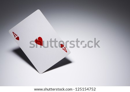Ace of Hearts playing card balancing on its corner. Gambling concept