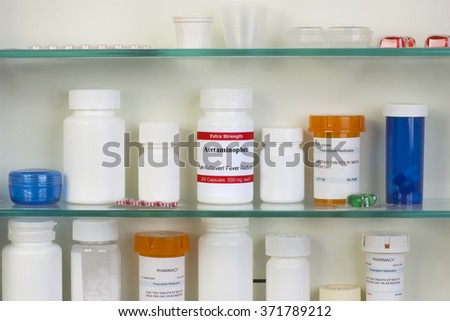 Acetaminophen in medicine cabinet.  Labels are all fictitious. - stock photo