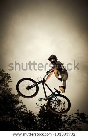 Achievement concept: Man flying high on a bike against the sky - stock photo