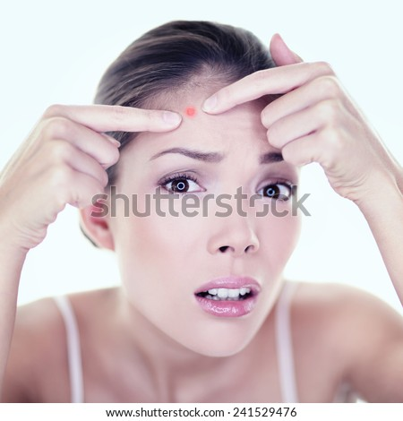 Acne pimple skin blemish spot skin care girl. Beauty care girl pressing on skin problem face. Woman with skin blemish looking at mirror isolated. Beautiful young Asian Caucasian female model. - stock photo