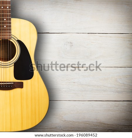 Acoustic guitar against vintage wooden background - stock photo