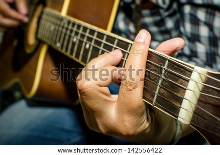 Acoustic guitar being played, Fingers holding a chord. - stock photo