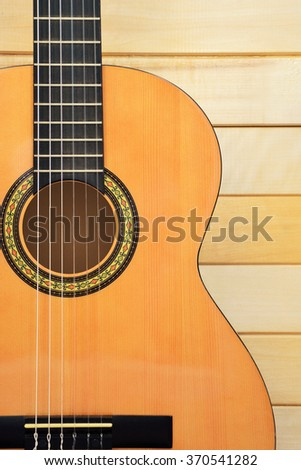 Acoustic guitar closeup front view on wooden background - stock photo