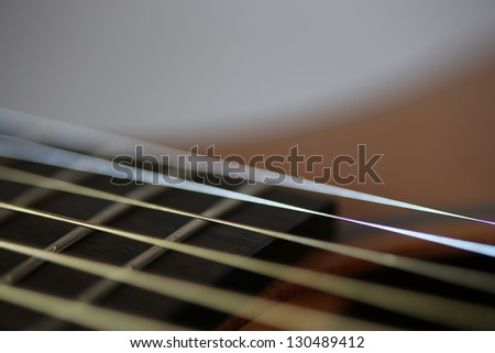 Acoustic guitar fretboard and strings closeup mostly unfocused simulating strings vibrating - stock photo