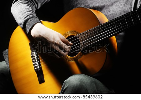 Acoustic guitar guitarist playing details. Musical instrument with performer hands - stock photo