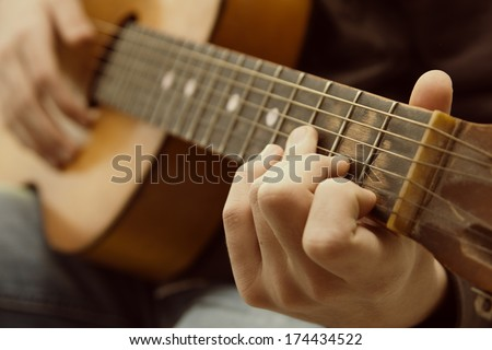 Acoustic guitar guitarist playing. Musical instrument with performer hands - stock photo