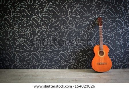 Acoustic guitar in empty room background - stock photo