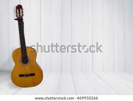 acoustic guitar leaning against the wall