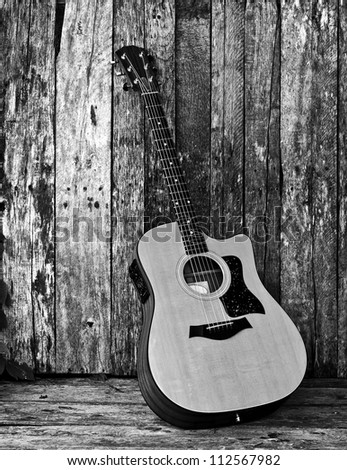 Acoustic guitar on a grunge wood backdrop, desaturated. - stock photo
