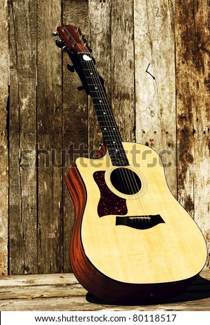 Acoustic guitar on a grunge wood backdrop in the sunshine with copy space. - stock photo