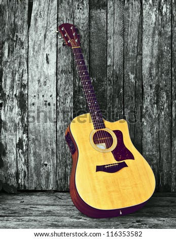 Acoustic guitar on a grunge wood  desaturated backdrop with copy space. - stock photo