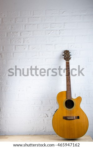 Acoustic Guitar on Background white brick with Space for messages