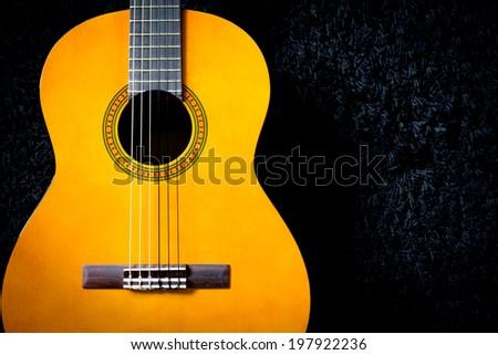 acoustic guitar on black carpet  - stock photo
