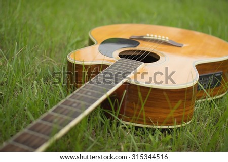Acoustic guitar on grass with vintage tone and soft focus - stock photo