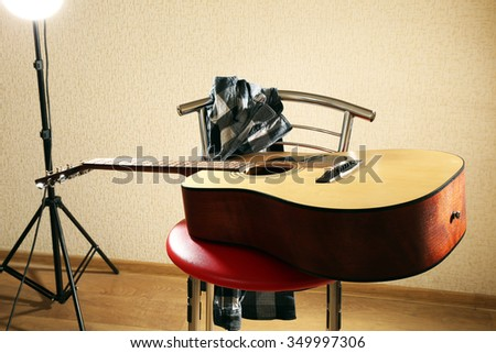 Acoustic guitar on red stool in the studio, close up