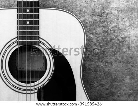 acoustic guitar on the background of a concrete wall close-up, monochrome.