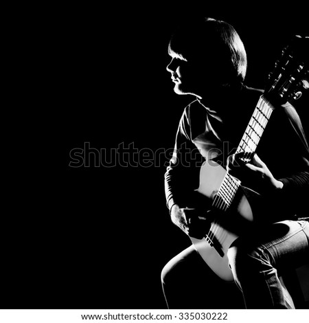 Acoustic guitar player guitarist. Classical guitar musical instrument concert playing in darkness - stock photo