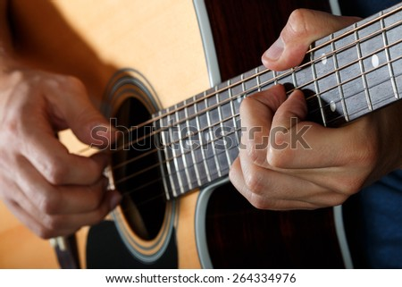 Acoustic guitar player performing song. Hands closeup - stock photo