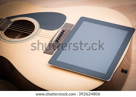 Acoustic guitar with digital tablet on the wooden table - stock photo