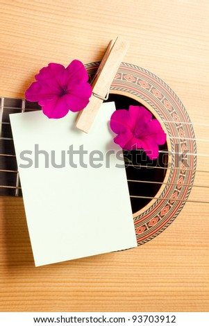 Acoustic guitar with flowers and blank card. Concept image for invitation to a romantic/musical event