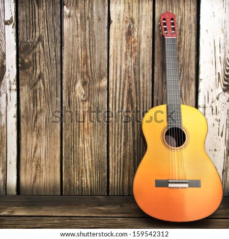 Acoustic wooden guitar leaning on a wooden fence. Advertisement with room for text or copy space.  - stock photo