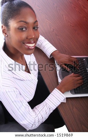 Acrican American Woman With Computer Sitting At Desk - stock photo