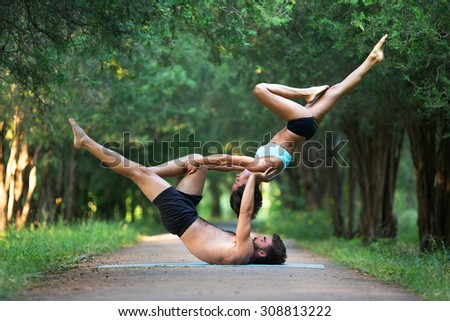 Acro yoga, two sporty people practice yoga in pair, couple doing stretching exercise in the garden