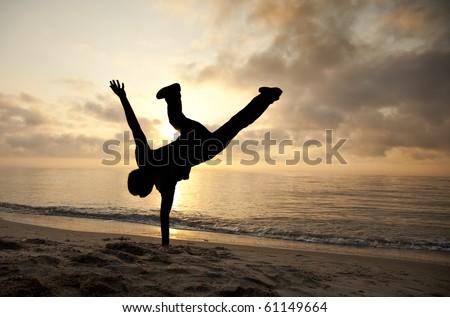 Acrobatic men on the sunset - stock photo