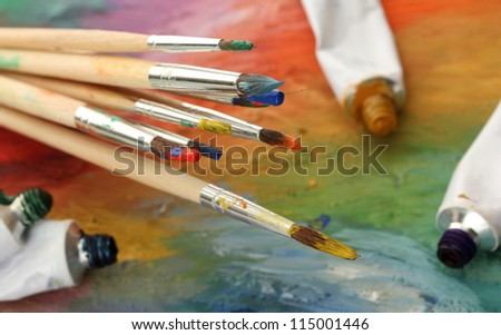 acrylic paint, paint tubes and brushes on wooden palette - stock photo